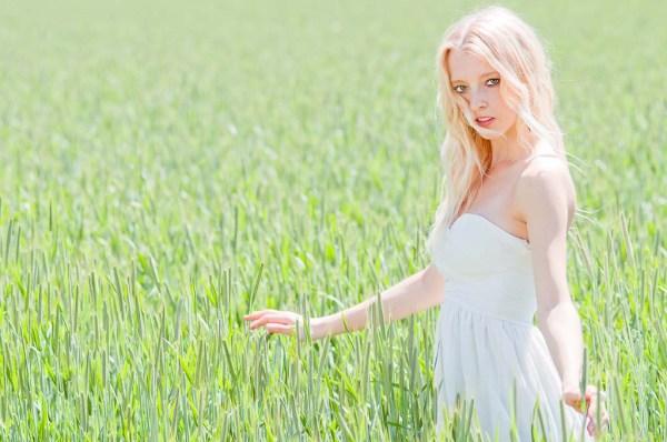 Carina steht in weißem Kleid im Feld